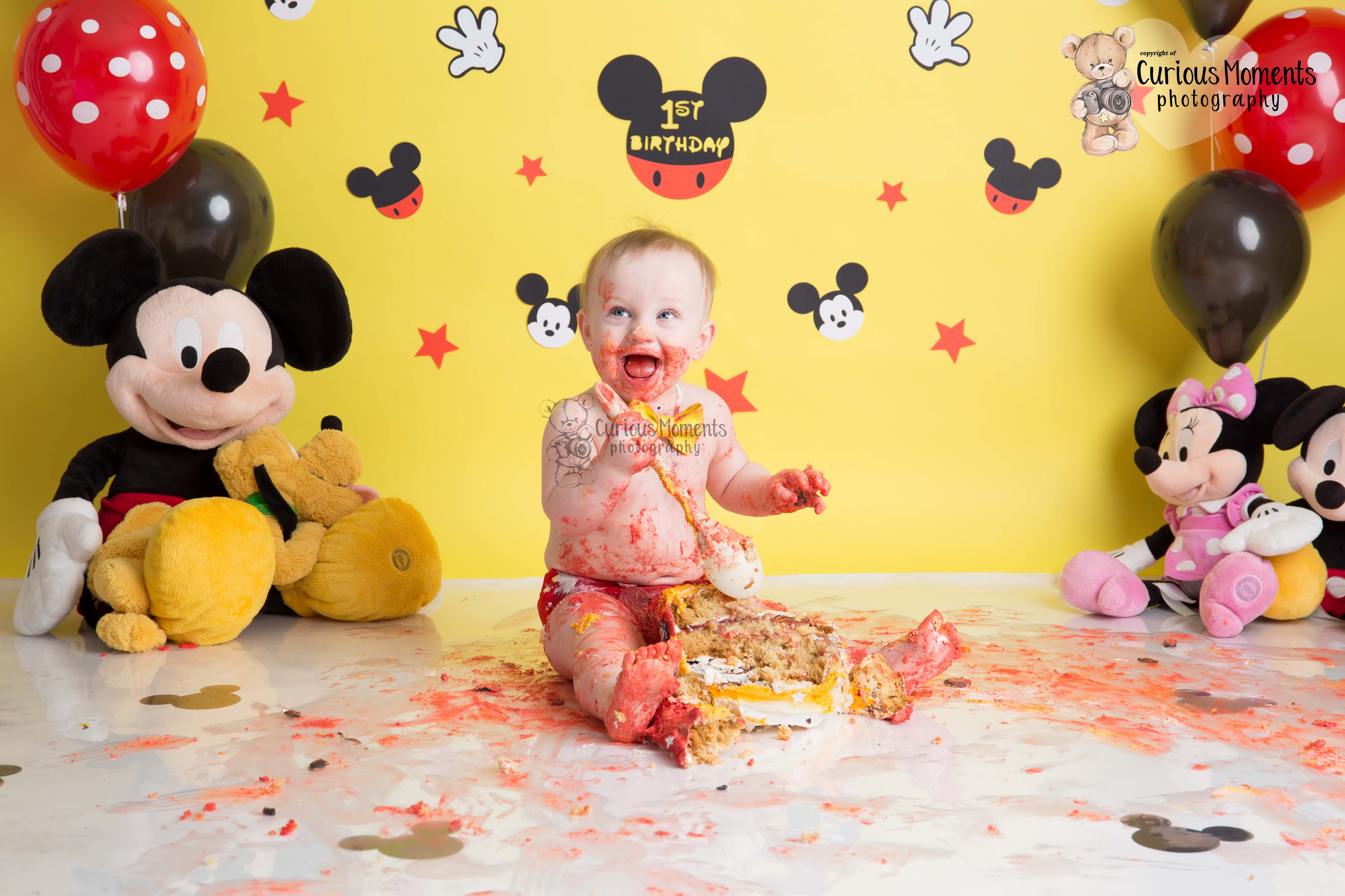 Baby covered in cake during his Mickey mouse cake smash photo shoot