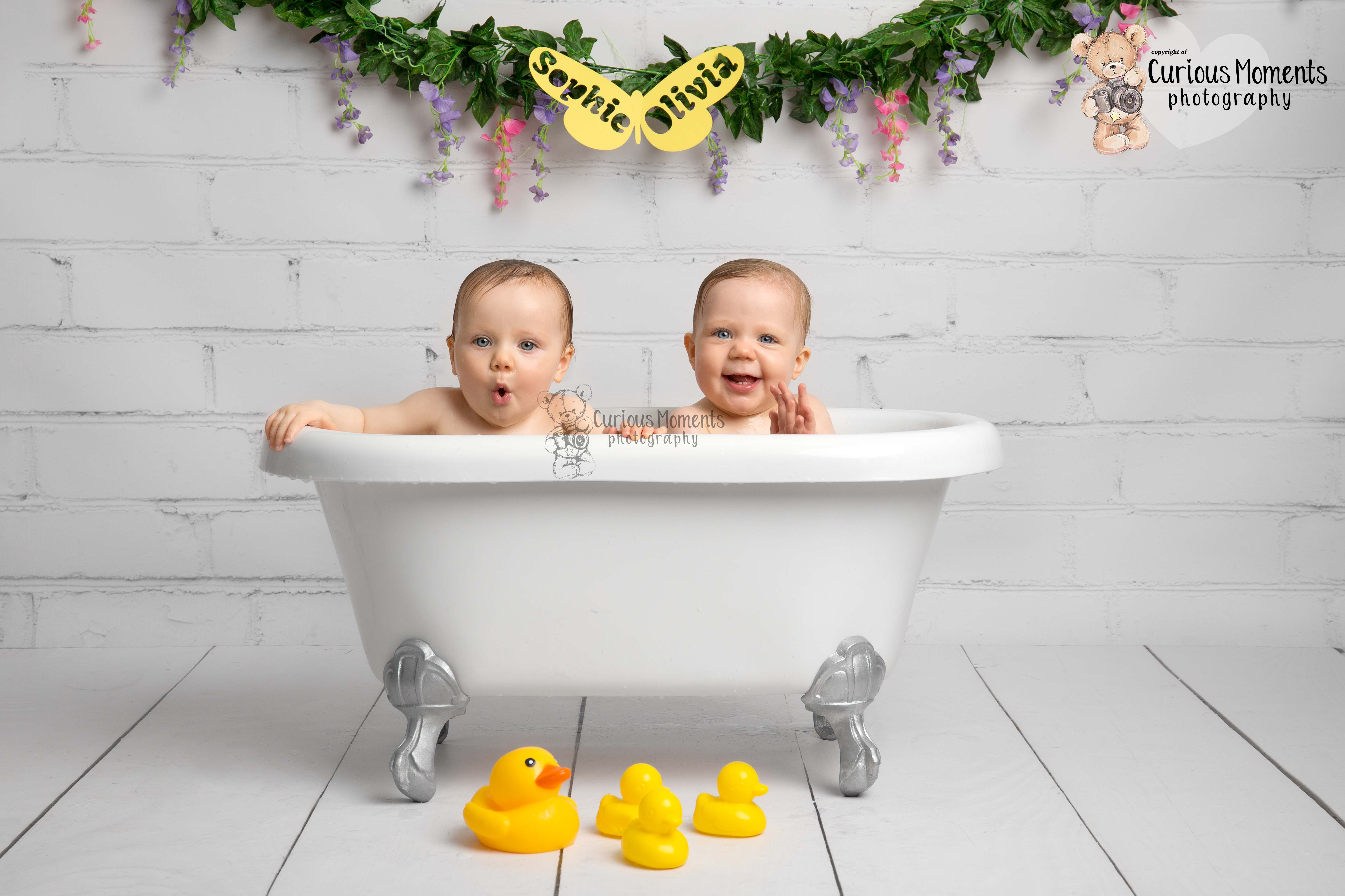 twin girls in roll top bath smiling and giggling