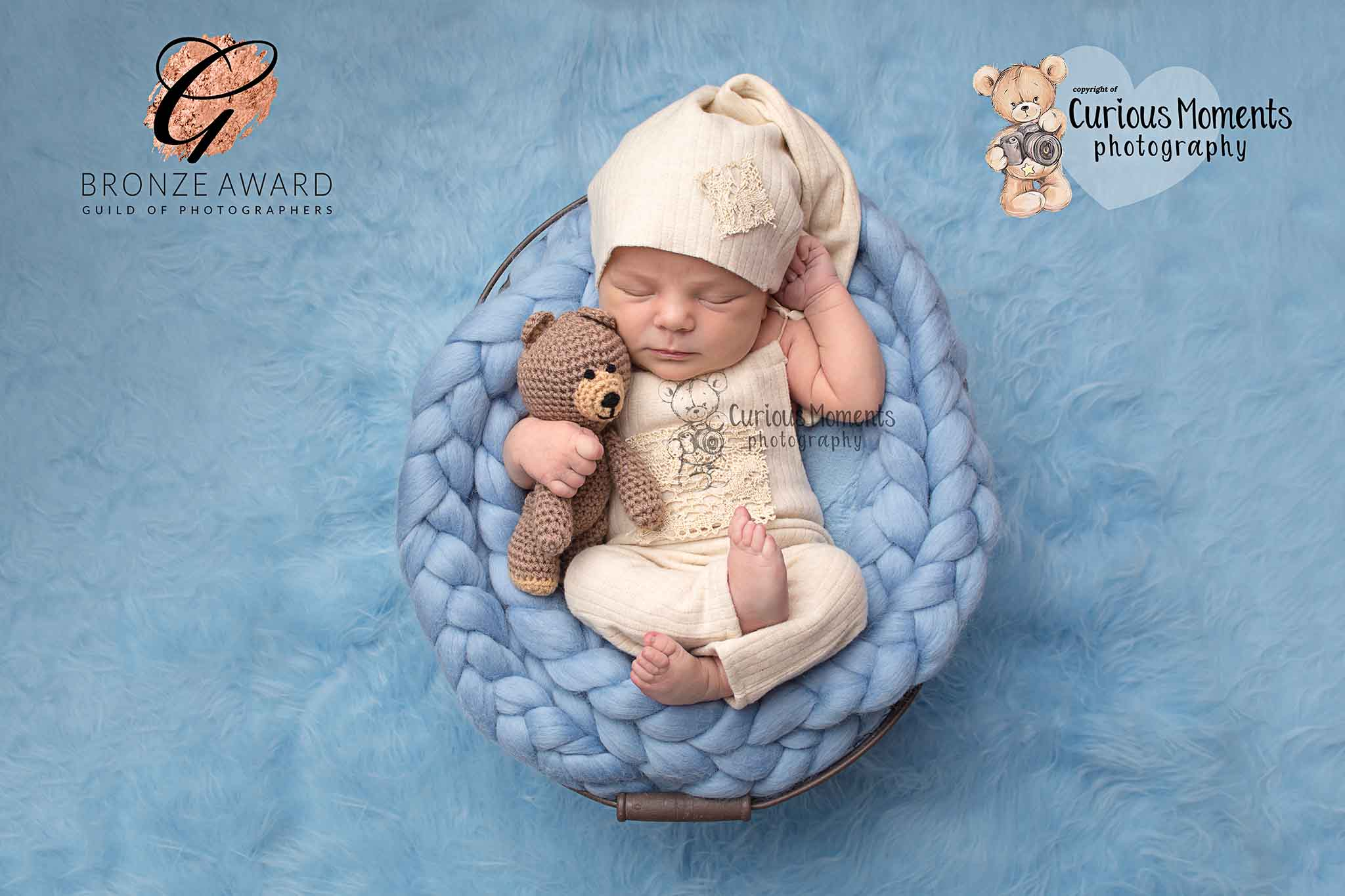 Award winning image by Baby Photographer Carmarthen of baby on blue background nestled into a blue plaited cushion in a basket cuddling a teddy during photo shoot with baby photographer carmarthen