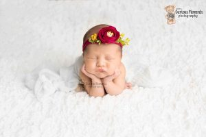 baby girl in head on hands pose on white background wearing red flower headband