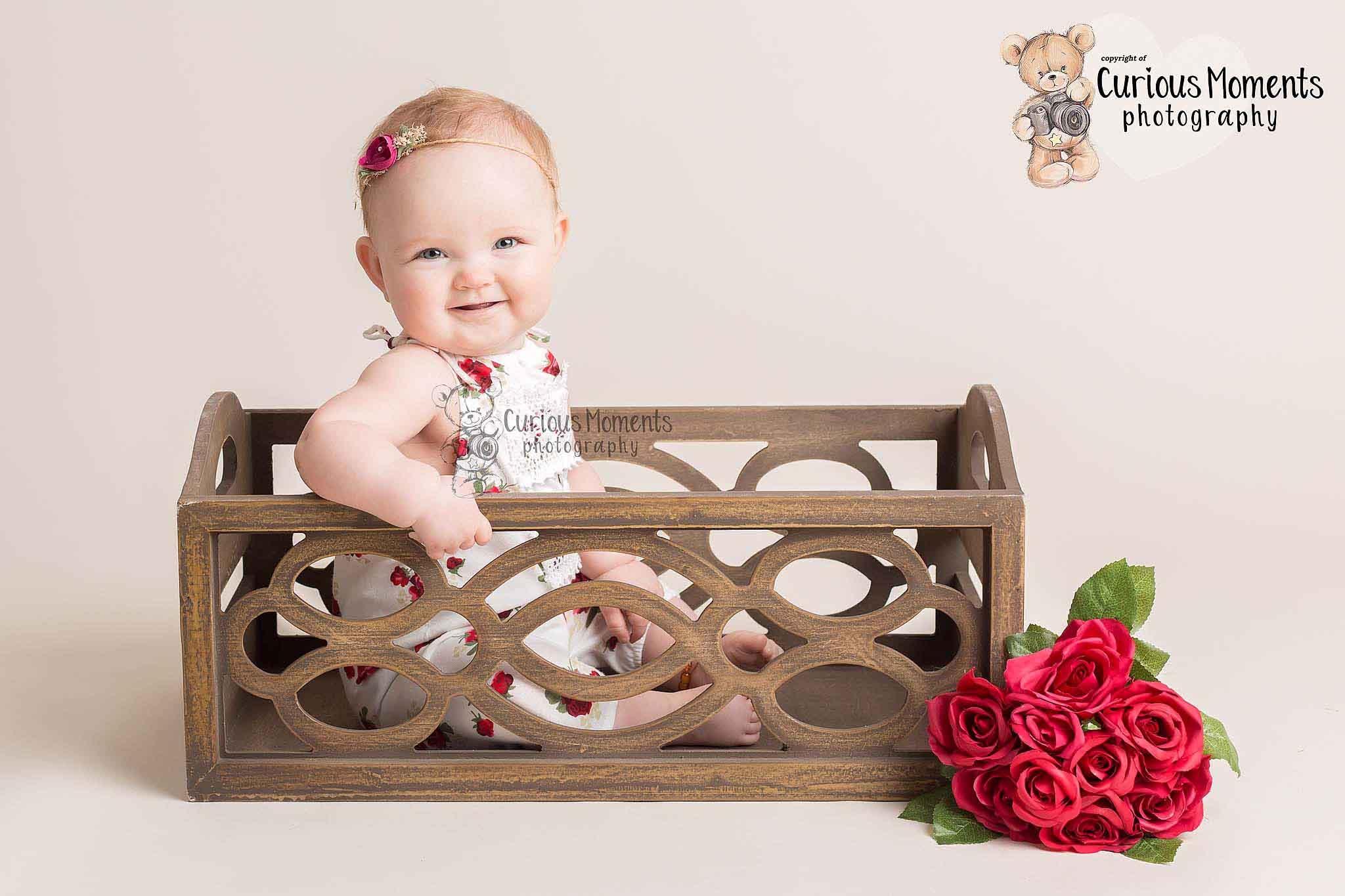 Baby girl smiling sitting in wooden crate with roses in her with Baby Photographer Pembrokeshire