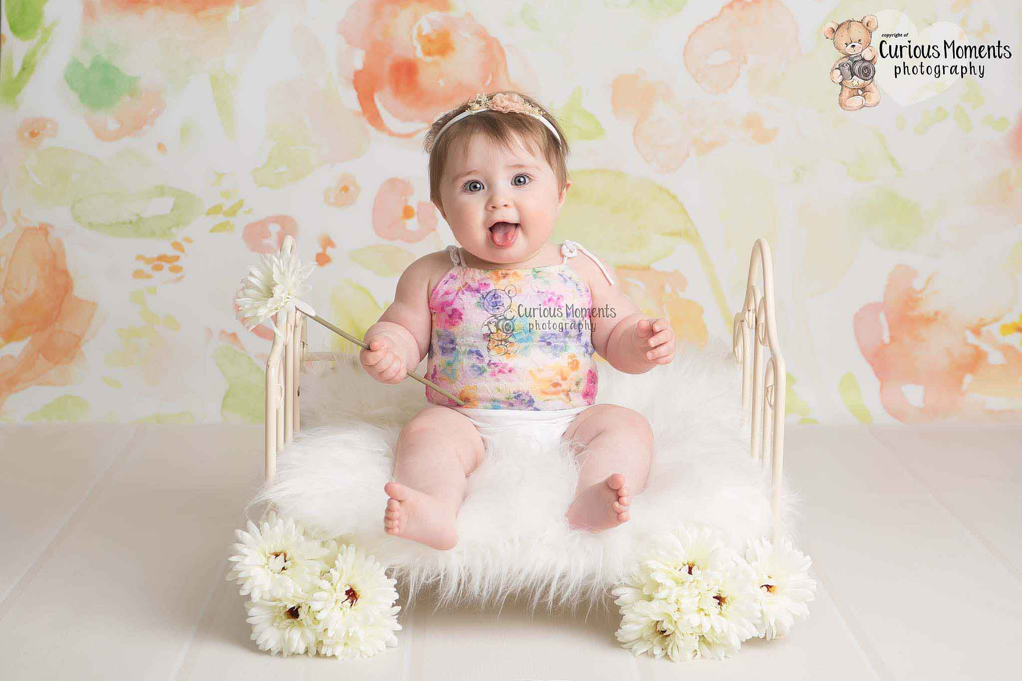 Cheeky baby girl in floral romper sticking out tongue while sitting on bed holding a flower in her photo shoot with Carmarthen baby photographer