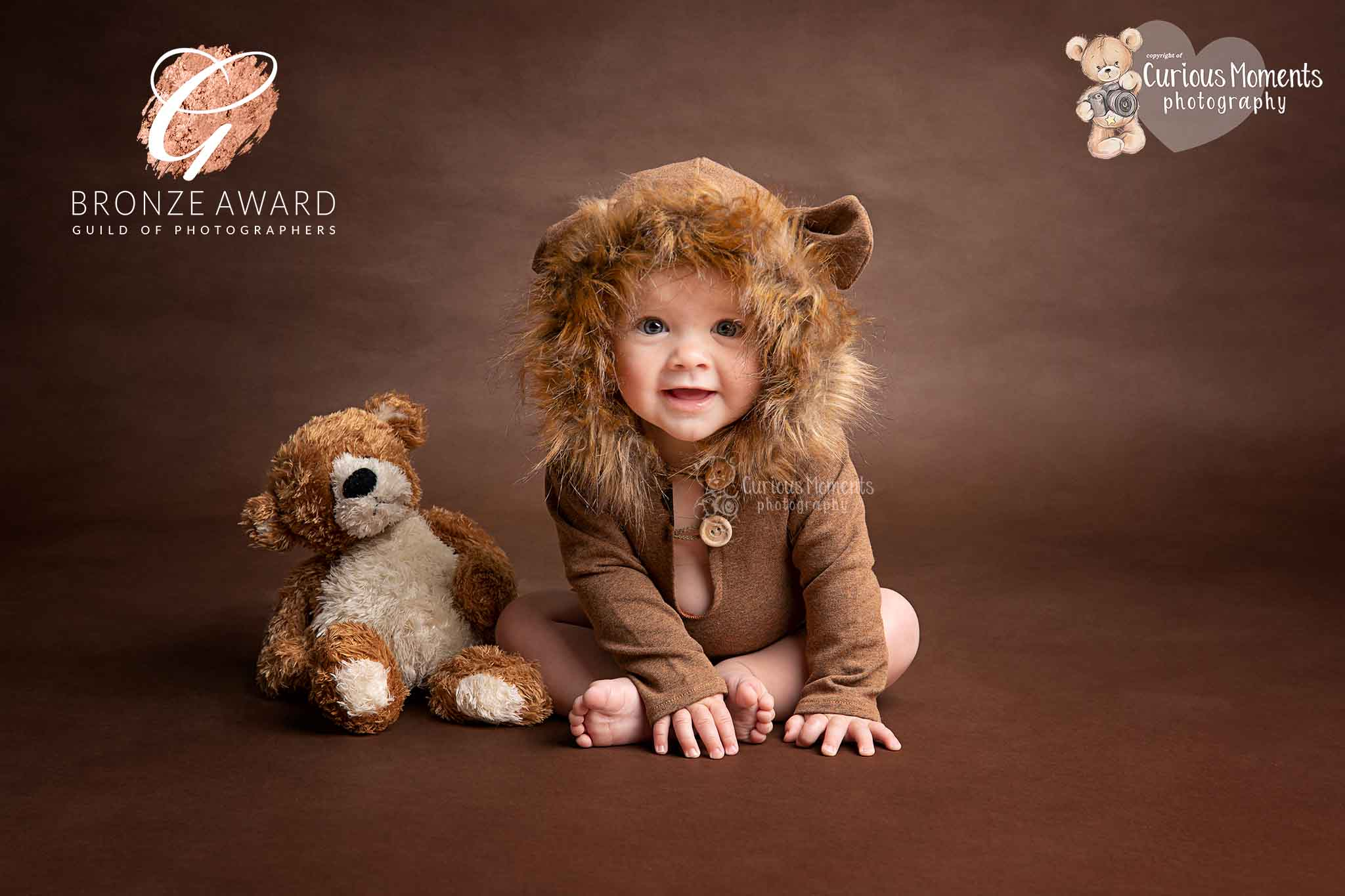 Award winning image of baby boy in a bear outfit sat next to a teddy on a brown background during photo shoot with pembrokeshire baby photographer