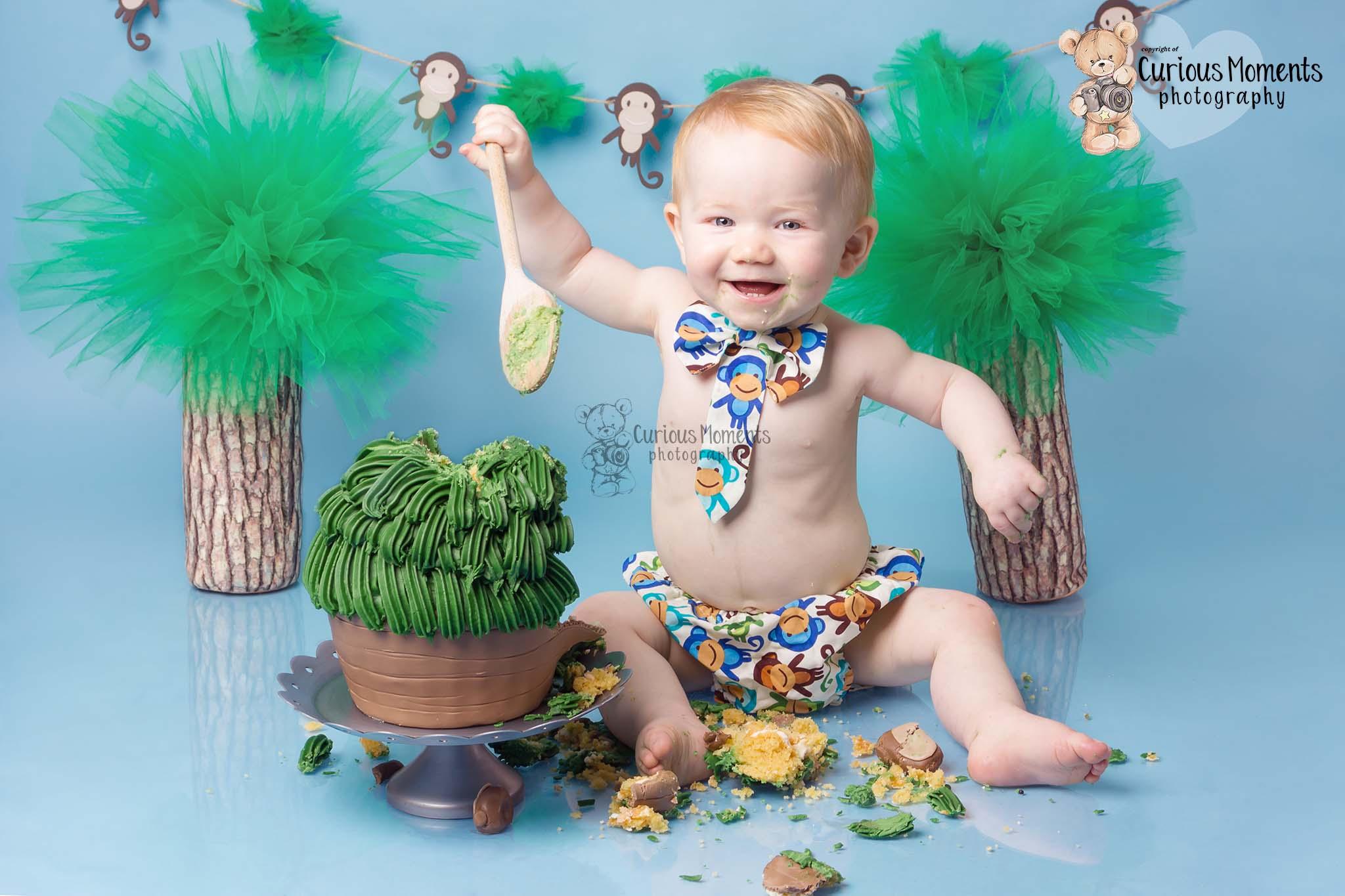 !st birthday photoshoot for little boy on blue background with ajungle Monkey themed cake smash with carmarthen photographer