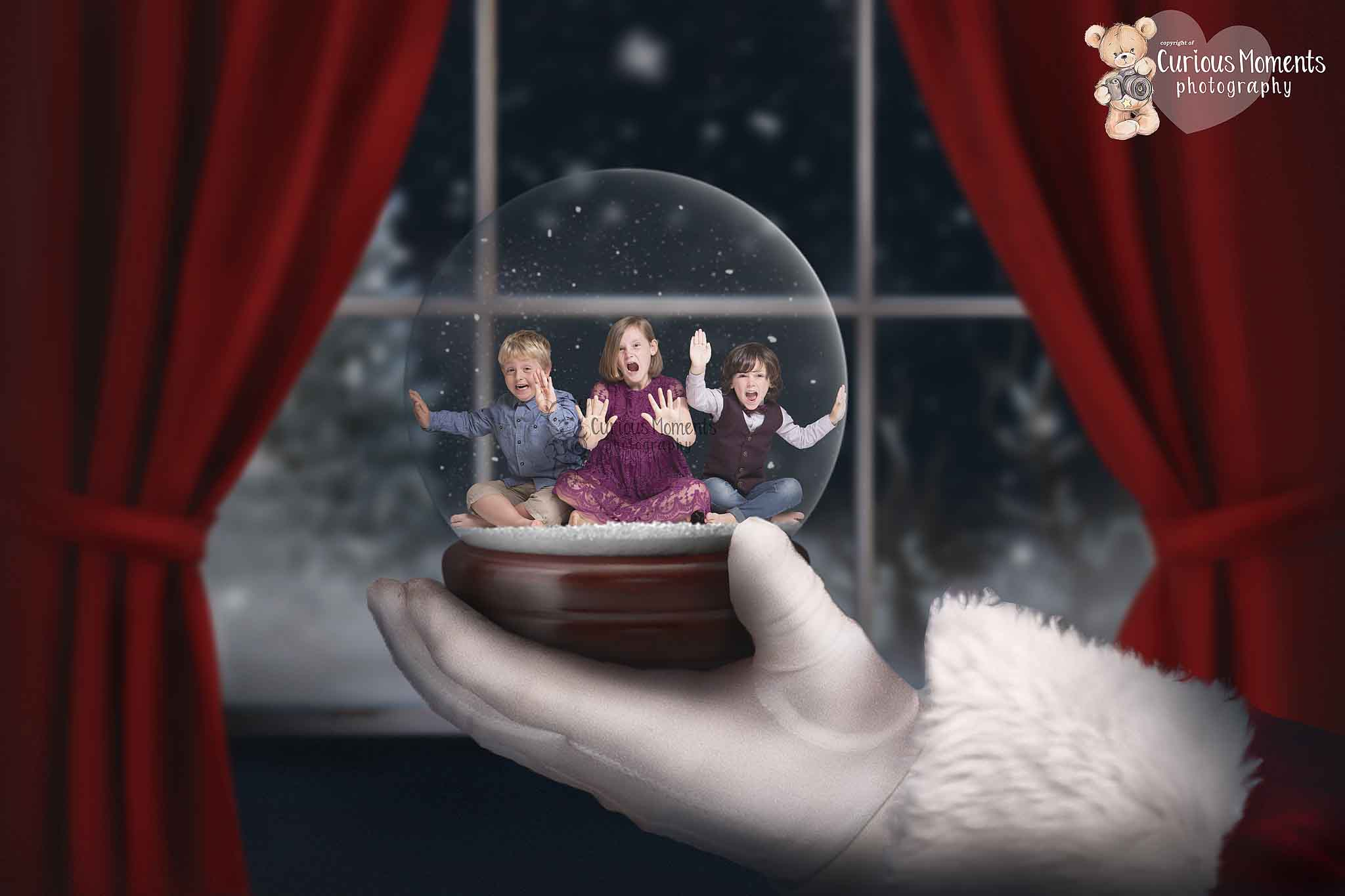 3 children in a snowglobe pretending to try and break free during xmas photo shoot