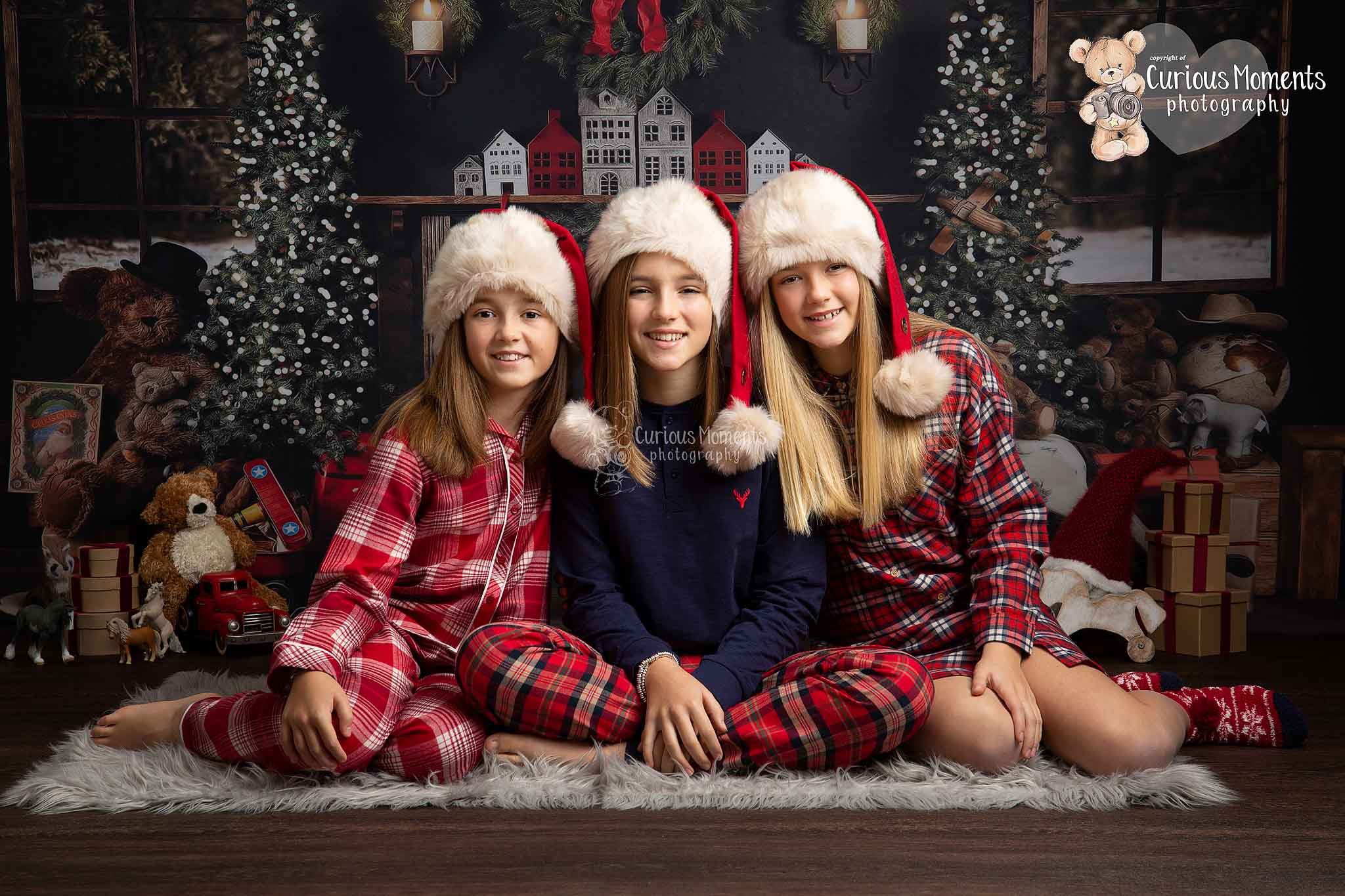 teenage girls in christmas pjs and christmas hats sat in a festive room with xmas trees, decortaions and presents during their chistmas mini session
