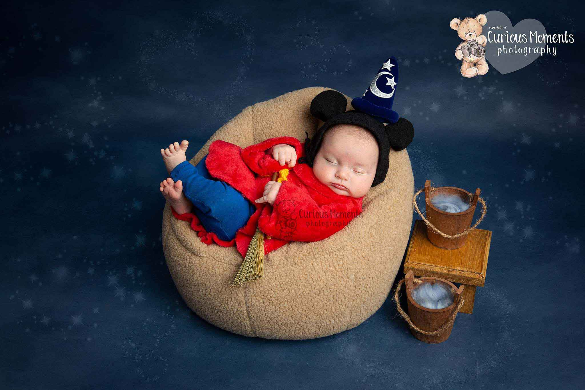 Fantasia inspired newborn photography session with baby sleeping in chair dressed as Mickey holding broom during his session in Carmarthenshire