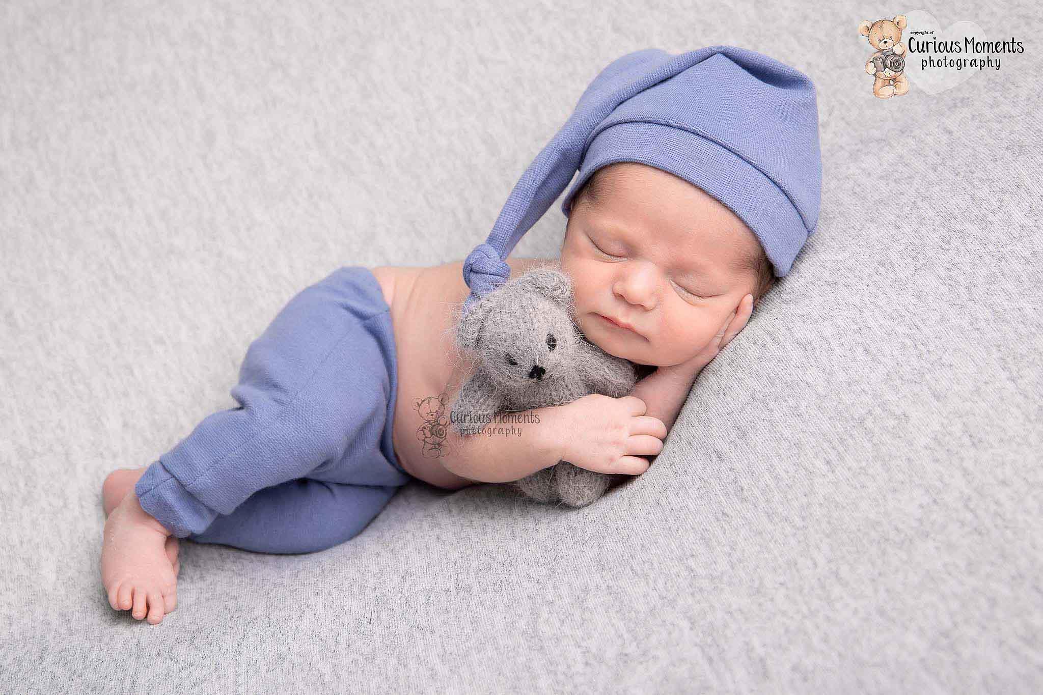 Newborn baby boy lying on side in sleepy hat hugging teddy