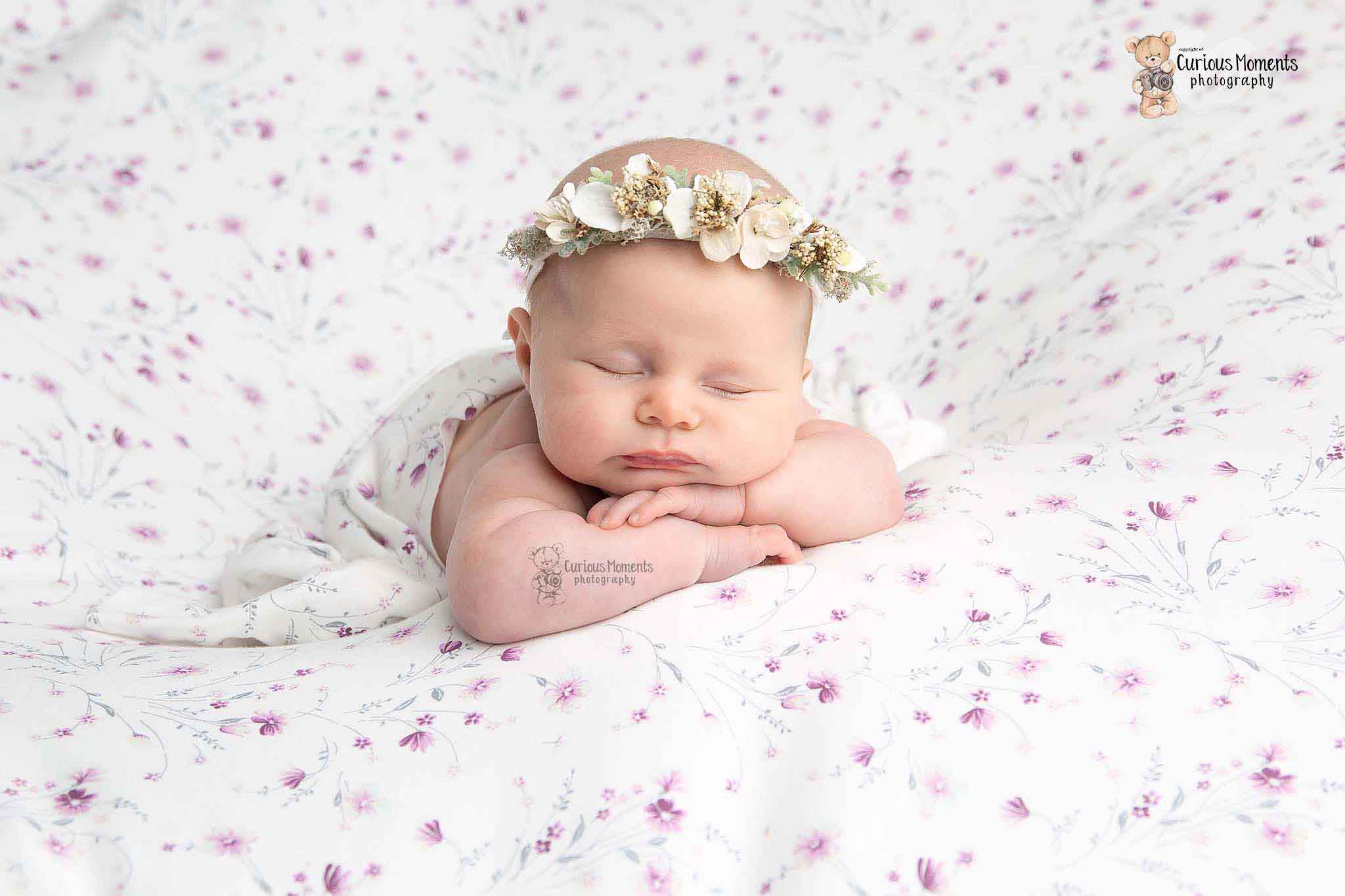 newborn baby girl in head on hands pose on a floral background and wearing a white floral crown