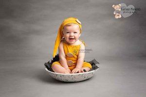 Baby bow wearning yellow romper and sleepy hat sat in a white mottled bowl on a grey background