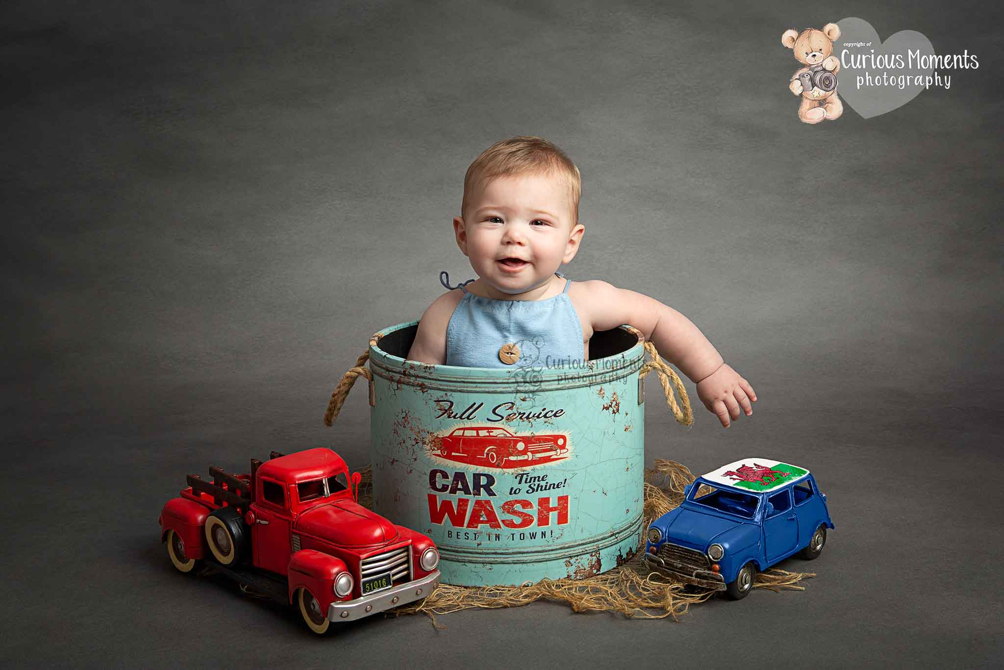 Baby boy say in a car wasy tub next to toy cars smiling at photographer