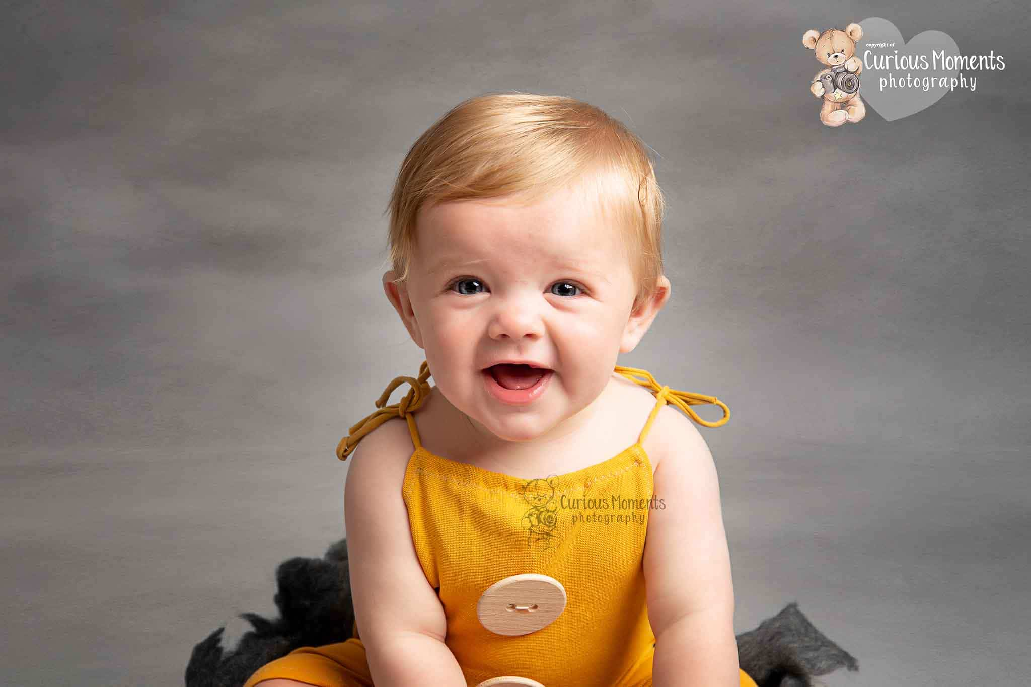 Close up of baby boy laughing wearing a muctard yellow romper