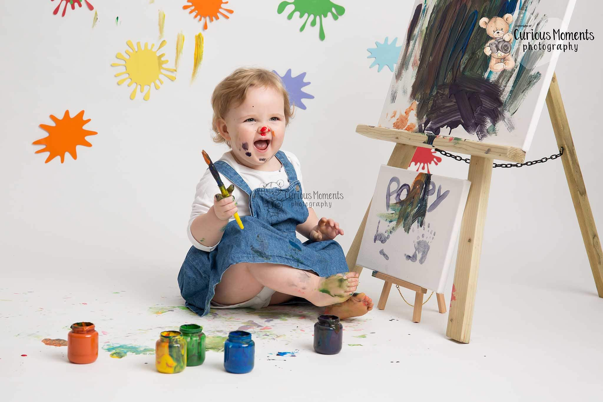 Toddler celebrating her 2nd birthday playing with paints during messy play photoshoot